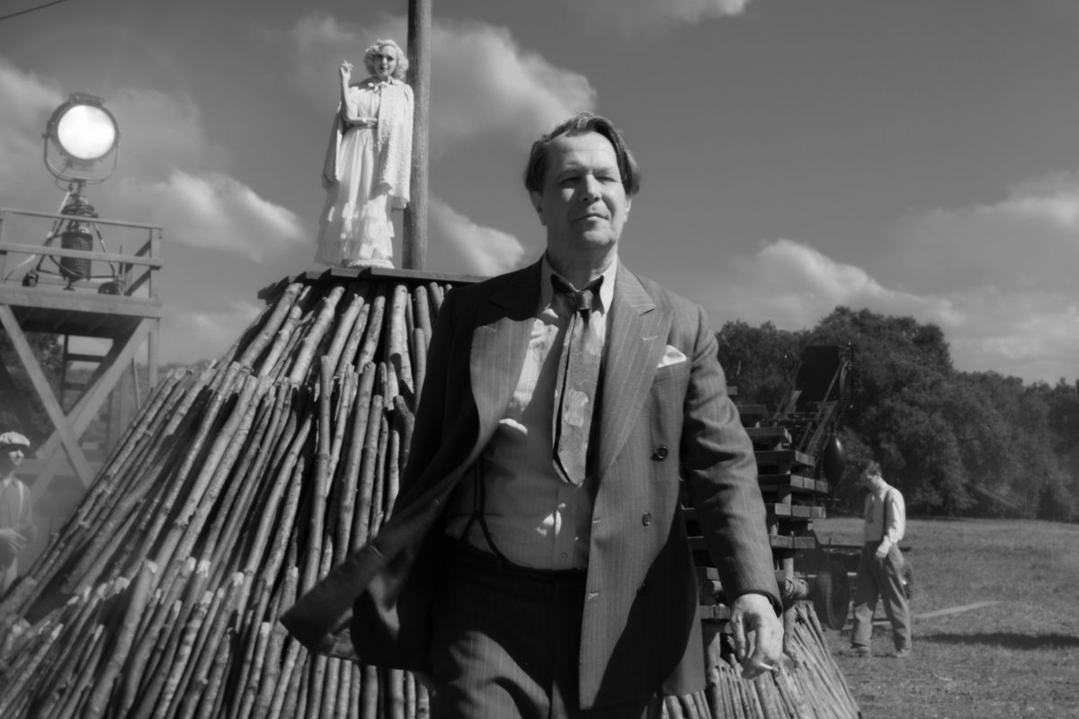 A black-and-white image of a man striding away from a movie set, an actress standing atop a pyre in the background.