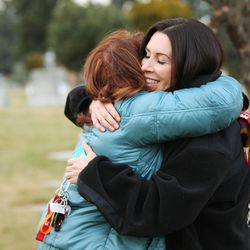 Angie Thompson, left,  gives Jenni Thompson a hug while visiting the grave of her husband, Bryce, at the Murray Cemetery in Murray Nov 19, 2014.  Several Thompson family members have died from cancer.