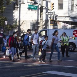 Several students and parents make their way toward Newark's Lafayette Street School on the first day of classes as a crossing guard halts traffic.