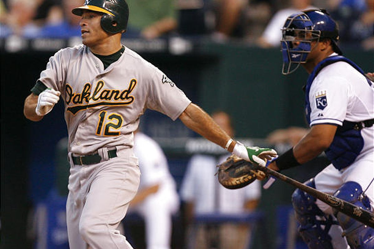 Oakland Athletics' Scott Hairston (12) drives the ball into left for a two-run single as Kansas City Royals catcher Brayan Pena looks on.