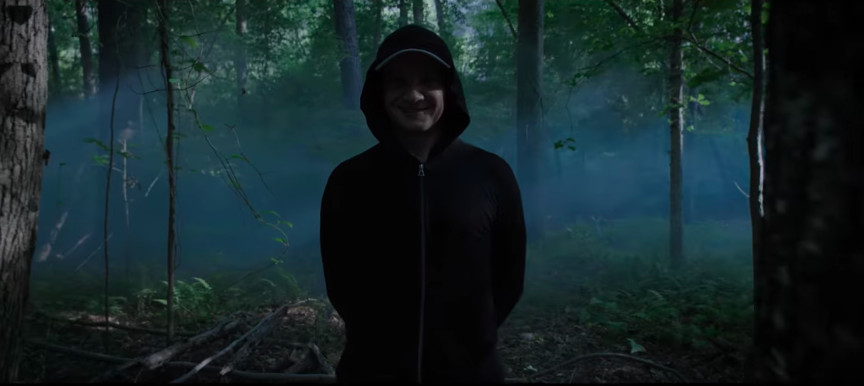 Jeremy Renner in the woods with his hands behind his back