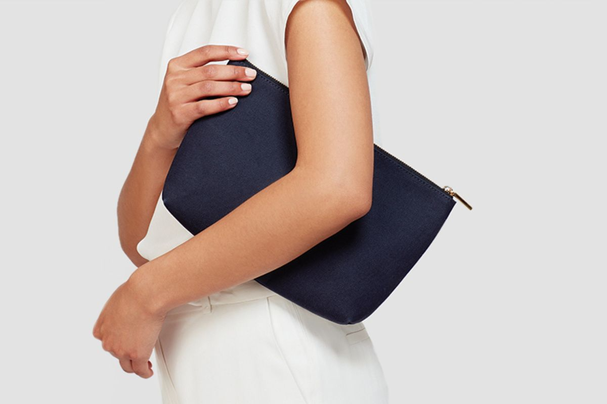 A woman holding a leather pouch