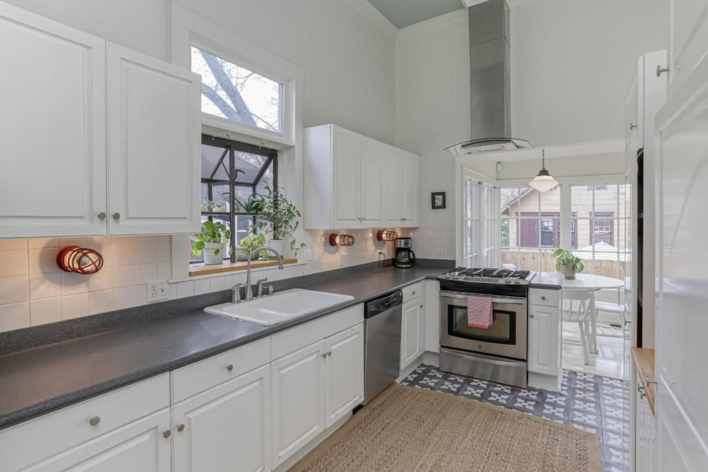 A huge white kitchen with a range hood and white cabinetry.