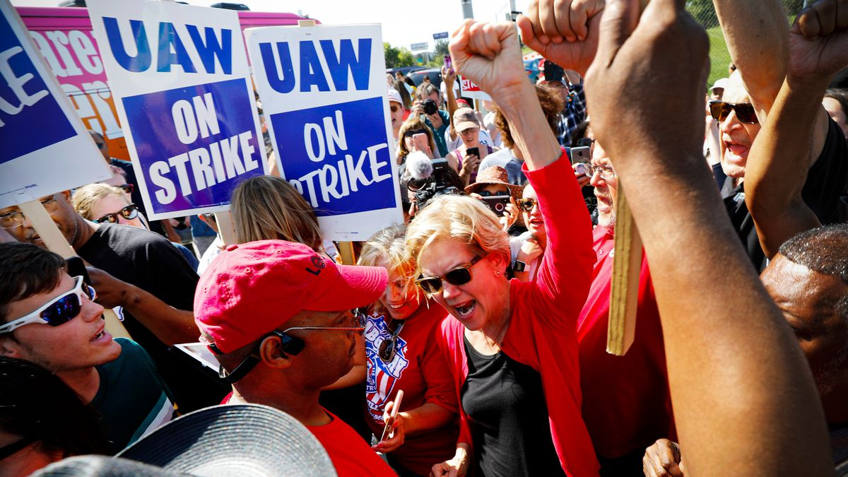 """Democratic presidential candidate Elizabeth Warren raises a fist and yells amid a crowd of workers holding signs that read """"UAW on strike."""""""