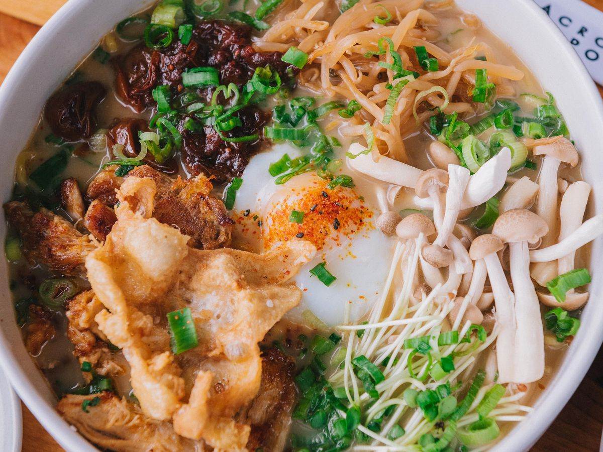 A closeup of a bowl of ramen with an egg, mushrooms, and lots of scallions in a red-tinted broth.