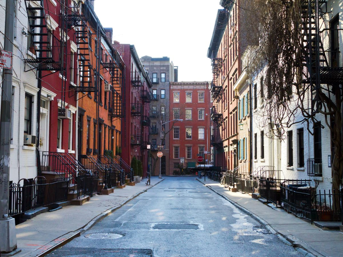 Gay Street in New York City. There are assorted attached colorful buildings that are on both sides of the street.