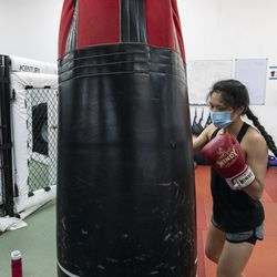 Jun Phan, a student at EFK Martial Arts, 5951 N. Clark St., hits the bag assigned to her during a boxing class on the first day of Illinois' Phase 4 reopening, Friday, June 26, 2020.