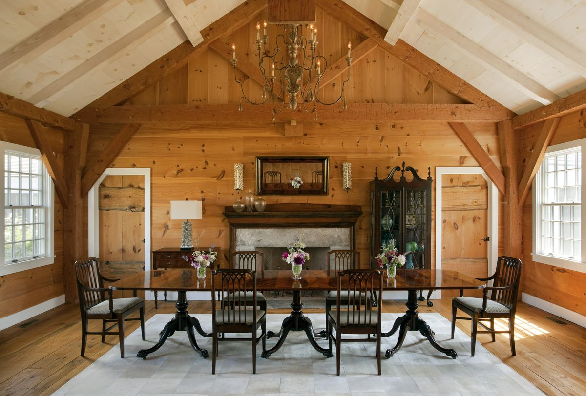 A dining roof with a black dining set, vaulted ceilings, and wood walls.
