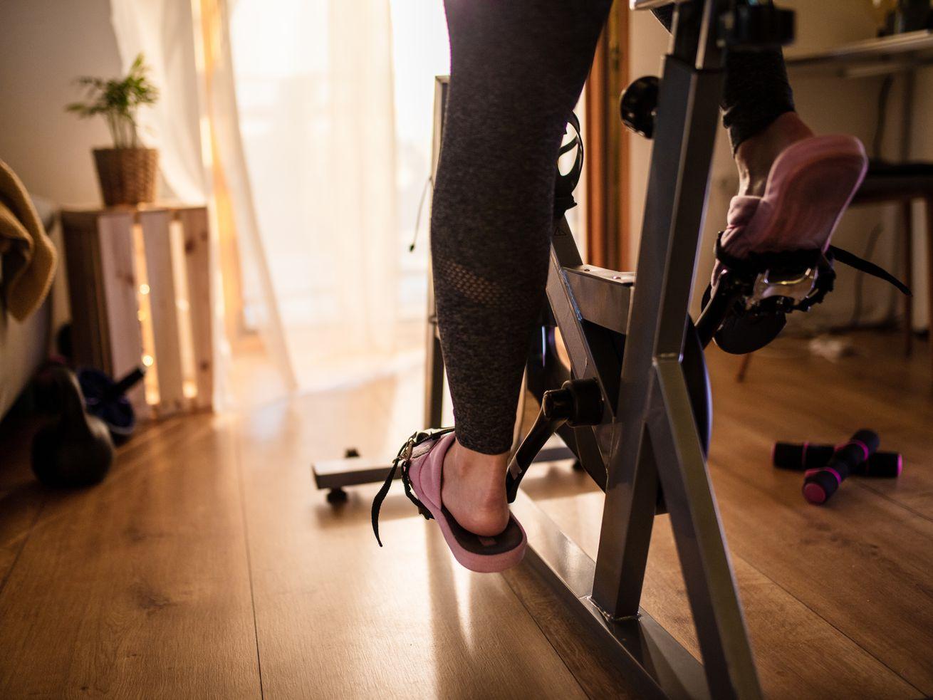 Les pieds d'une femme sur un vélo d'entraînement à domicile.