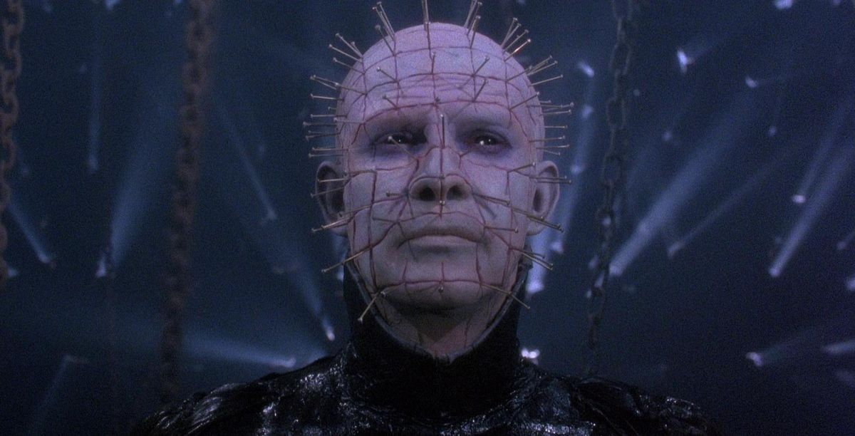 A close-up facial shot of Pinhead, the pale-skinned, nail-faced central antagonist from the Hellraiser movies.