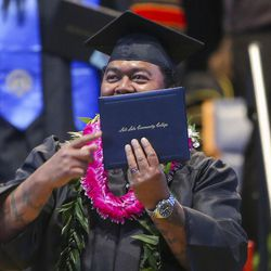 A Salt Lake Community College graduate points to his diploma during the 2017 commencement ceremony at the Maverik Center in West Valley City on Friday, May 5, 2017.