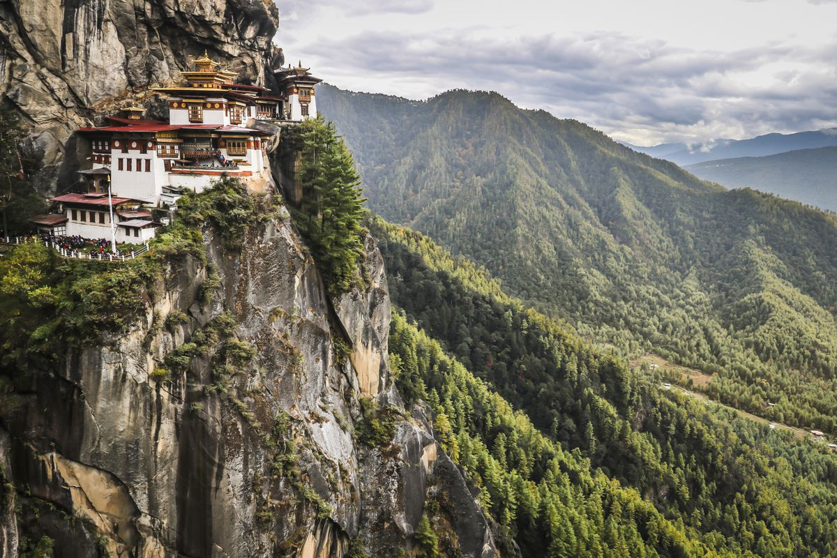"""The exterior of <span data-author=""""843"""">Paro Taktsang in Bhutan. The facade is white with multiple spires on the roof. The temple is situated high up on the edge of a cliff. There are mountains in the distance.</span>"""