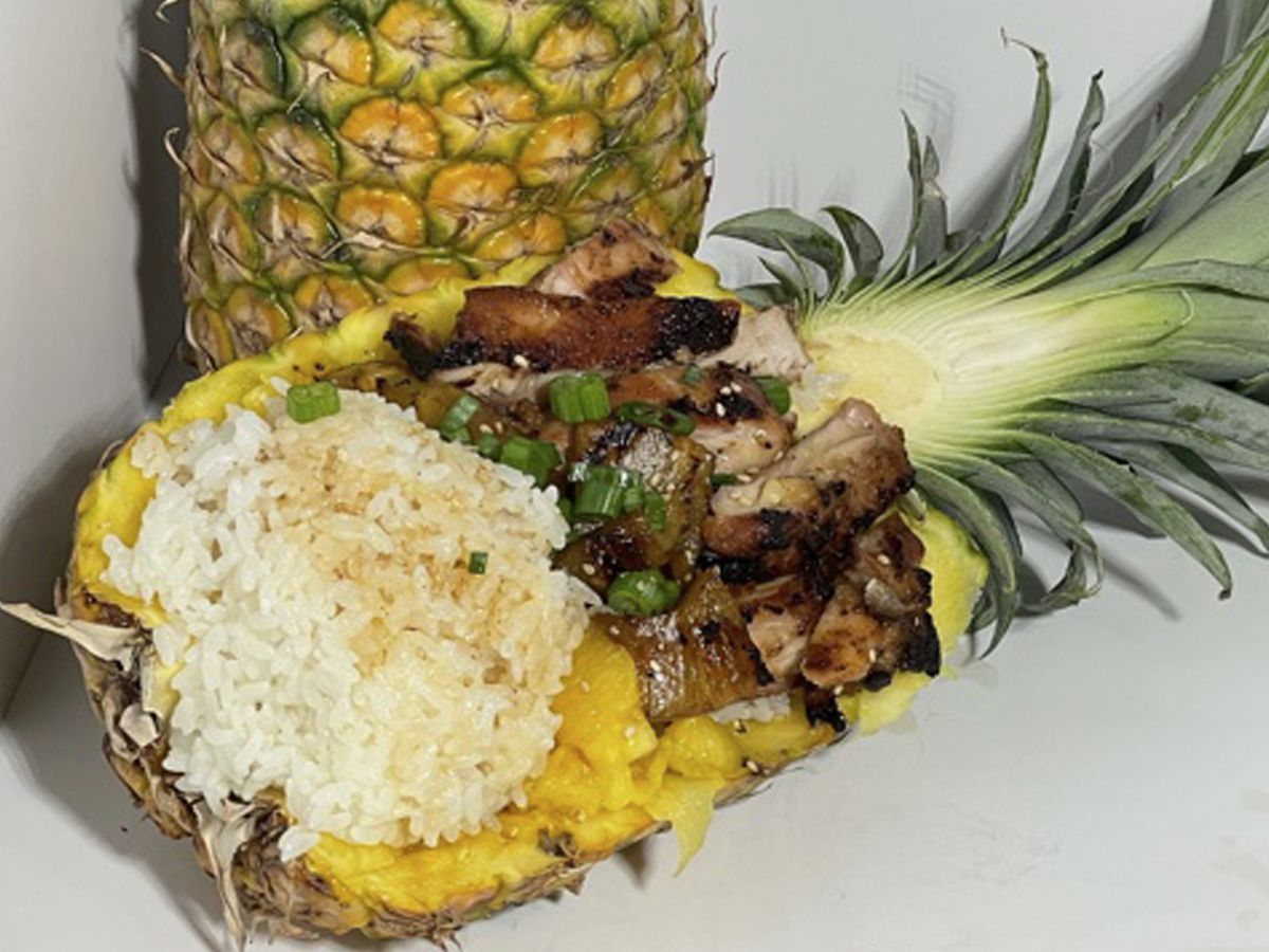 A halved pineapple viewed from the side stuffed with a stomach-sized wad of white rice with teriyaki sauce, above which is glazed chicken, and the green top of the pineapple is still on