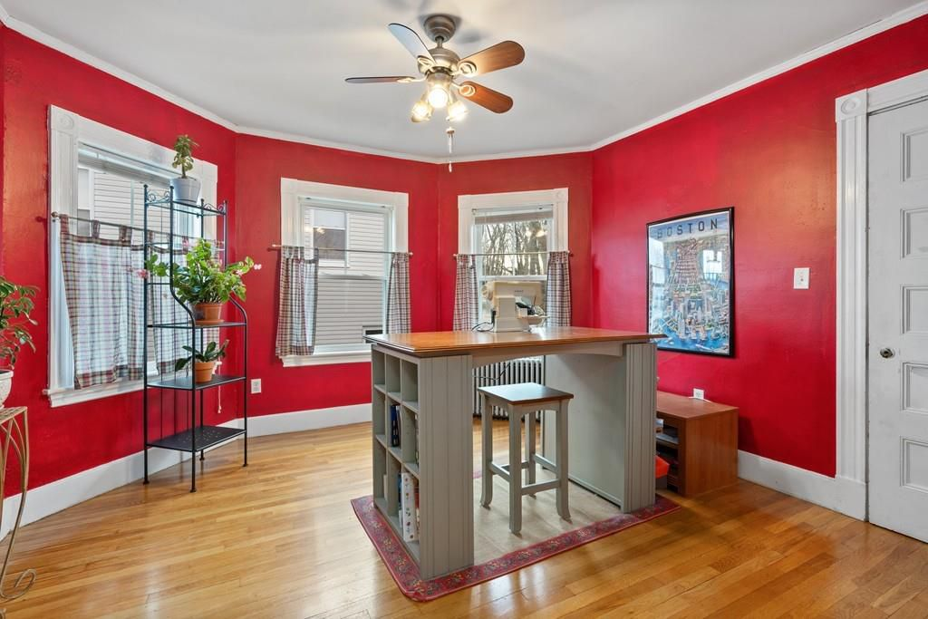 A bright room with lots of natural light and a high table with a stool tucked underneath.