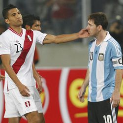Peru's Josepmir Ballon, left, pats the face of Argentina's Lionel Messi during a 2014 World Cup qualifying soccer game in Lima, Peru, Tuesday, Sept. 11, 2012.