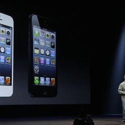 Phil Schiller, Apple's senior vice president of worldwide marketing, speaks in front of an image of the iPhone 5 during an Apple event in San Francisco, Wednesday, Sept. 12, 2012. (AP Photo/Jeff Chiu)