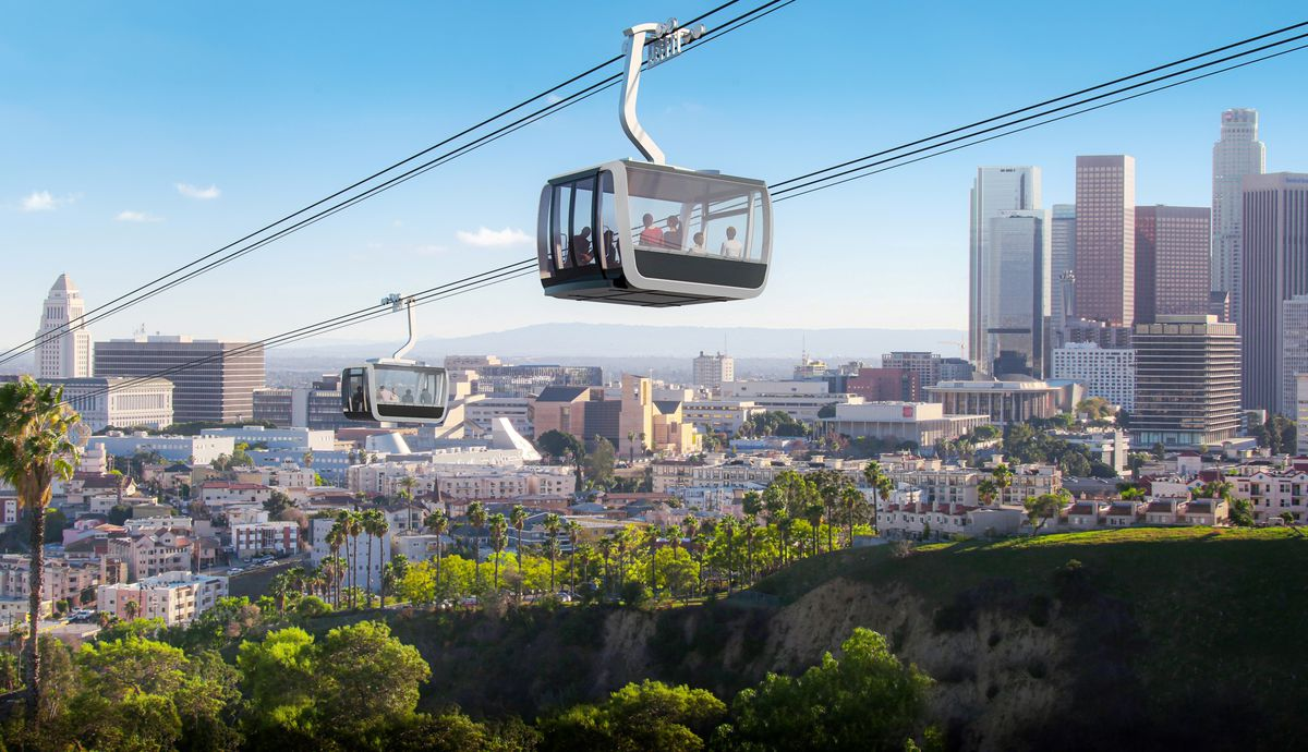 A rendering of a gondola with two cabins carrying passengers as it sails through the hills of L.A in front of the buildings of Downtown, including City Hall and skyscrapers.