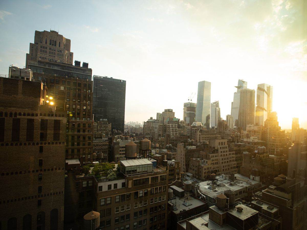 The New York City skyline with the sun setting behind it.