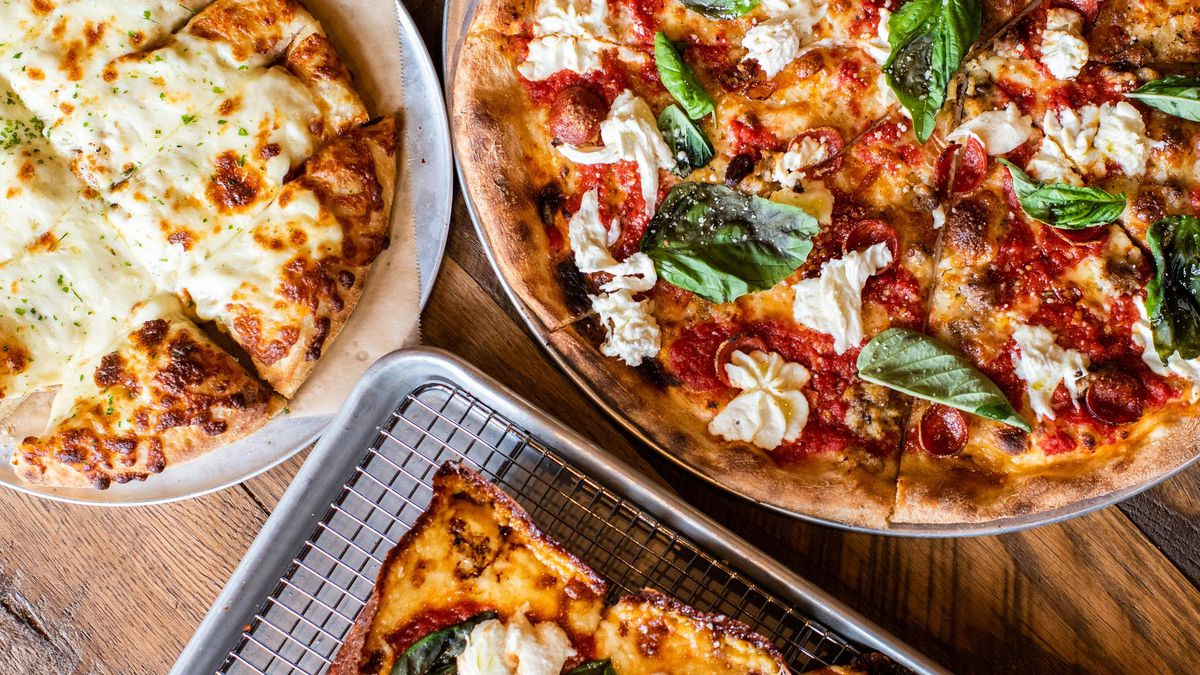 A plate of cheesy bread, a margherita pizza, and a Detroit-Style margherita pizza