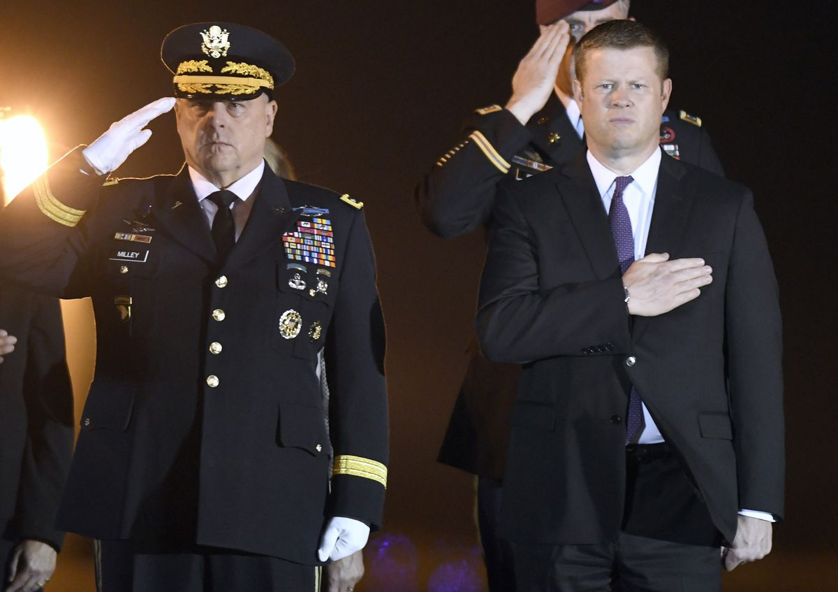 Army Chief of Staff Gen. Mark Milley (left) and Secretary of the Army Ryan McCarthy stand as the remains of Spc. Michael I. Nance are brought off a plane at Dover Air Force Base in Delaware Wednesday.