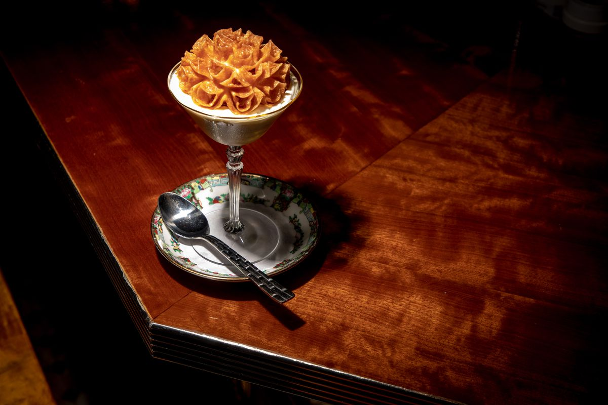 A lotus cookie sits atop a chalice of banana rum pudding, which sits on the corner of the mahogany bar