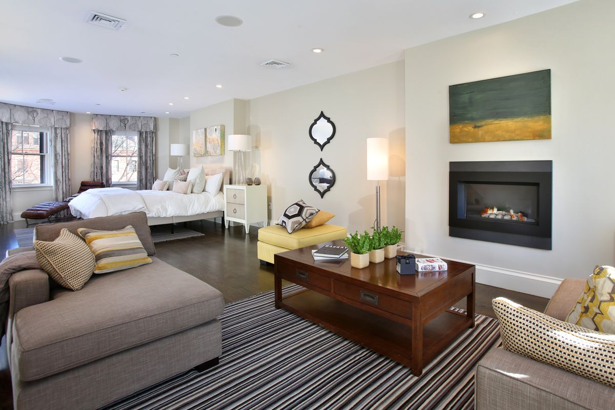 A main bedroom suite with a sitting area in front of a glass fireplace, and there's a bed in the background.