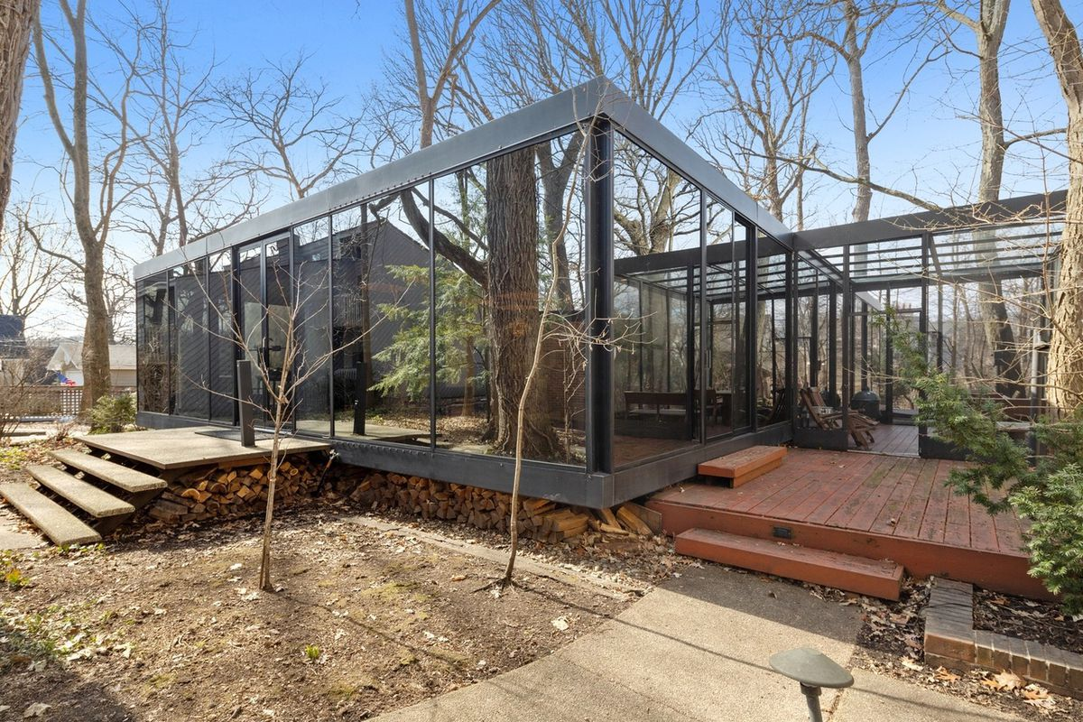 A boxy glass house with dark metal framing with a floating entry staircase and side porch surrounded by tall trees.