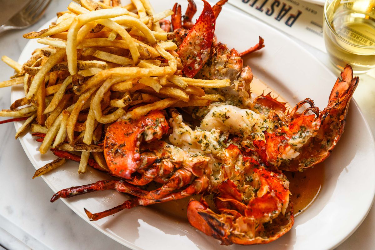 A pile of golden fries sit next to a crimson lobster, slathered in garlic butter