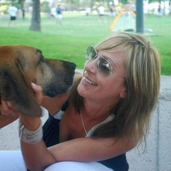 In this 2011 photo released by Sniff Pet Candles, Jenn Mohr, founder of Sniff Pet Candles, pets Rufus her 8-year-old Rhodesian ridgeback rescue dog in Miami, Fla. Mohr says she can't forgive Republican presidential hopeful Mitt Romney for making his dog ride on top of the car during a 1983 family trip to Canada. But many dog owners feel the whole doggone issue is a distraction.