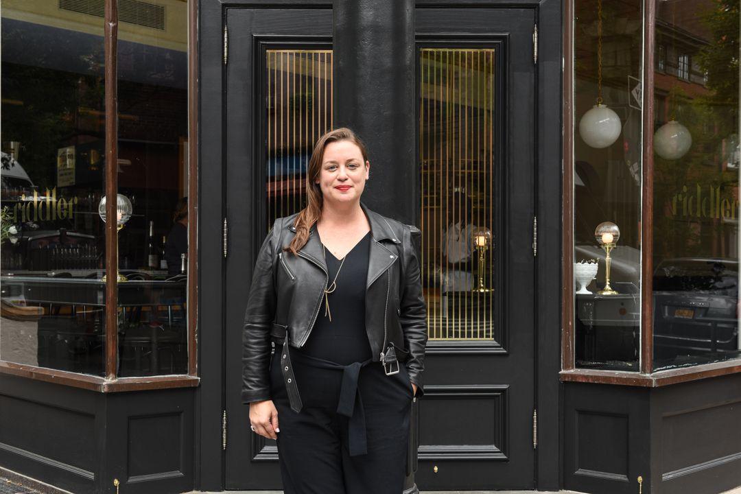 Jen Pelka, dressed in all black, stands in front of the black door at her West Village Champagne bar the Riddler
