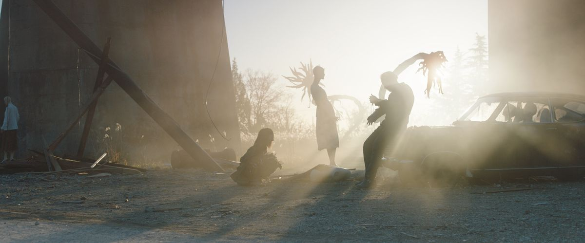 shadowy figures stand in a dustbowl near a mannequin in Prisoners of the Ghostland