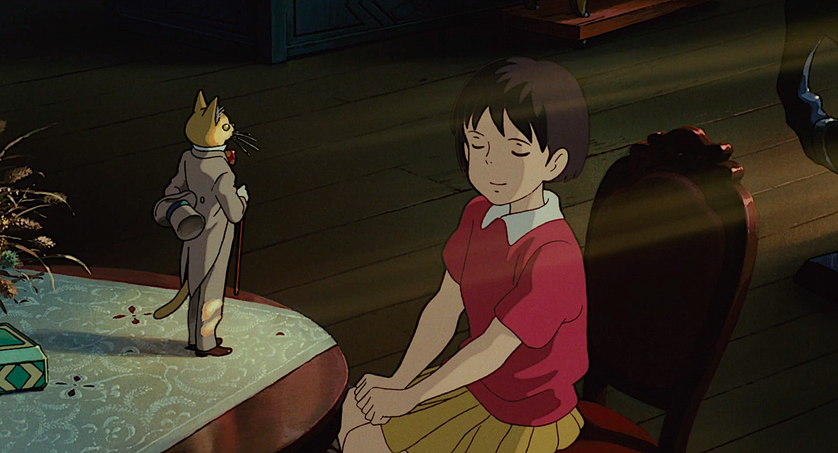 A girl with her eyes closed sits in a dark room at sunset with sunbeams falling on her, facing a little statue of a cat in a suit.