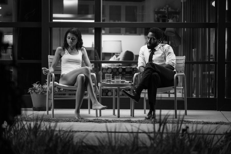 A man and a woman sit on a back porch.