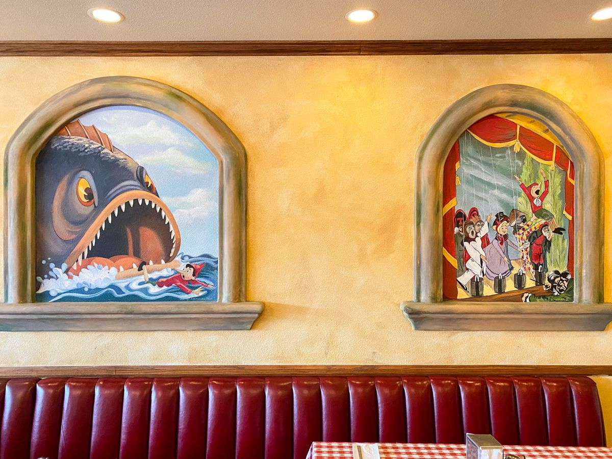 Pinocchio art in an Italian restaurant with a red booth below.