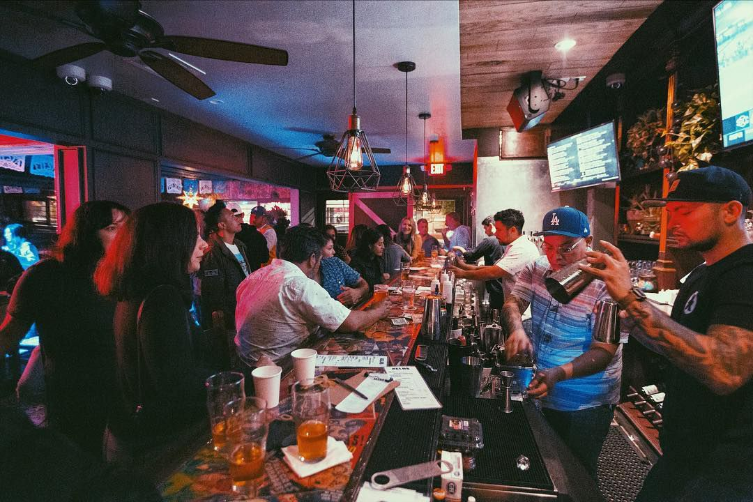 A packed bar with neon vibes as bartenders reach for cash.
