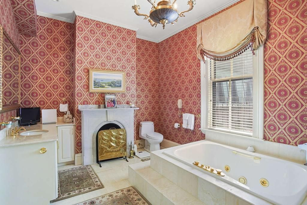 A sizable bathroom with a vanity, a fireplace, and a soaking tub.