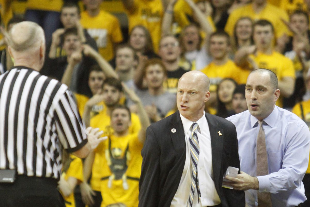 Illinois assistant head coach Dustin Ford (right) restrains John Groce from destroying this referee.