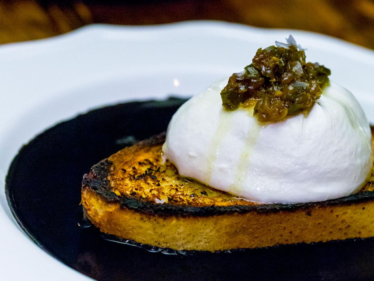 A white plate with dark squid ink pooled at the center. A crusty piece of toast with white burrata placed on top sits in the middle of the dish.