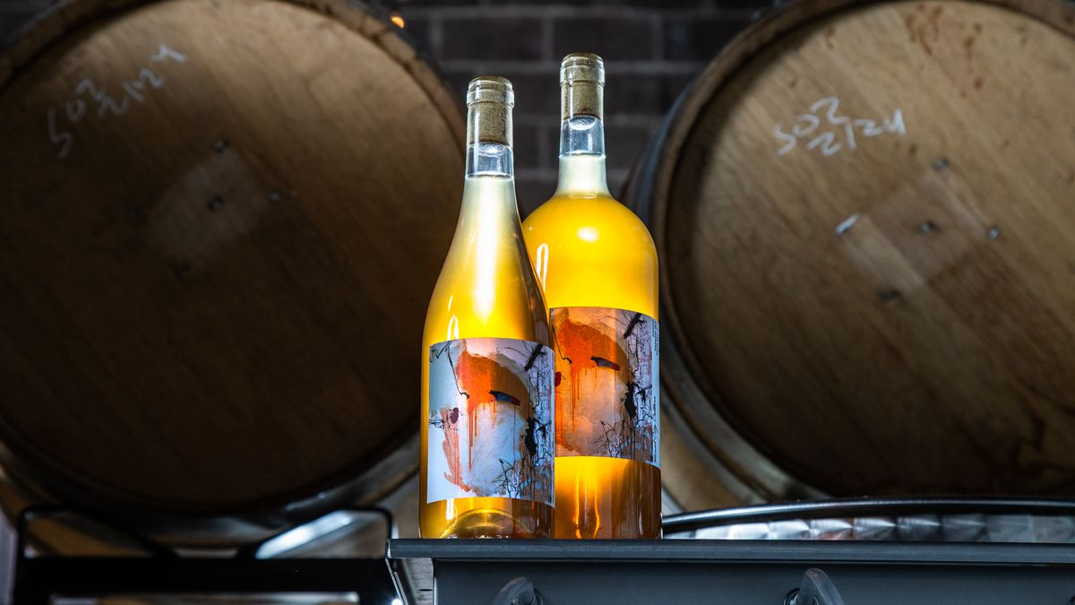 two bottles of white wine sitting on a table in front of wine barrels