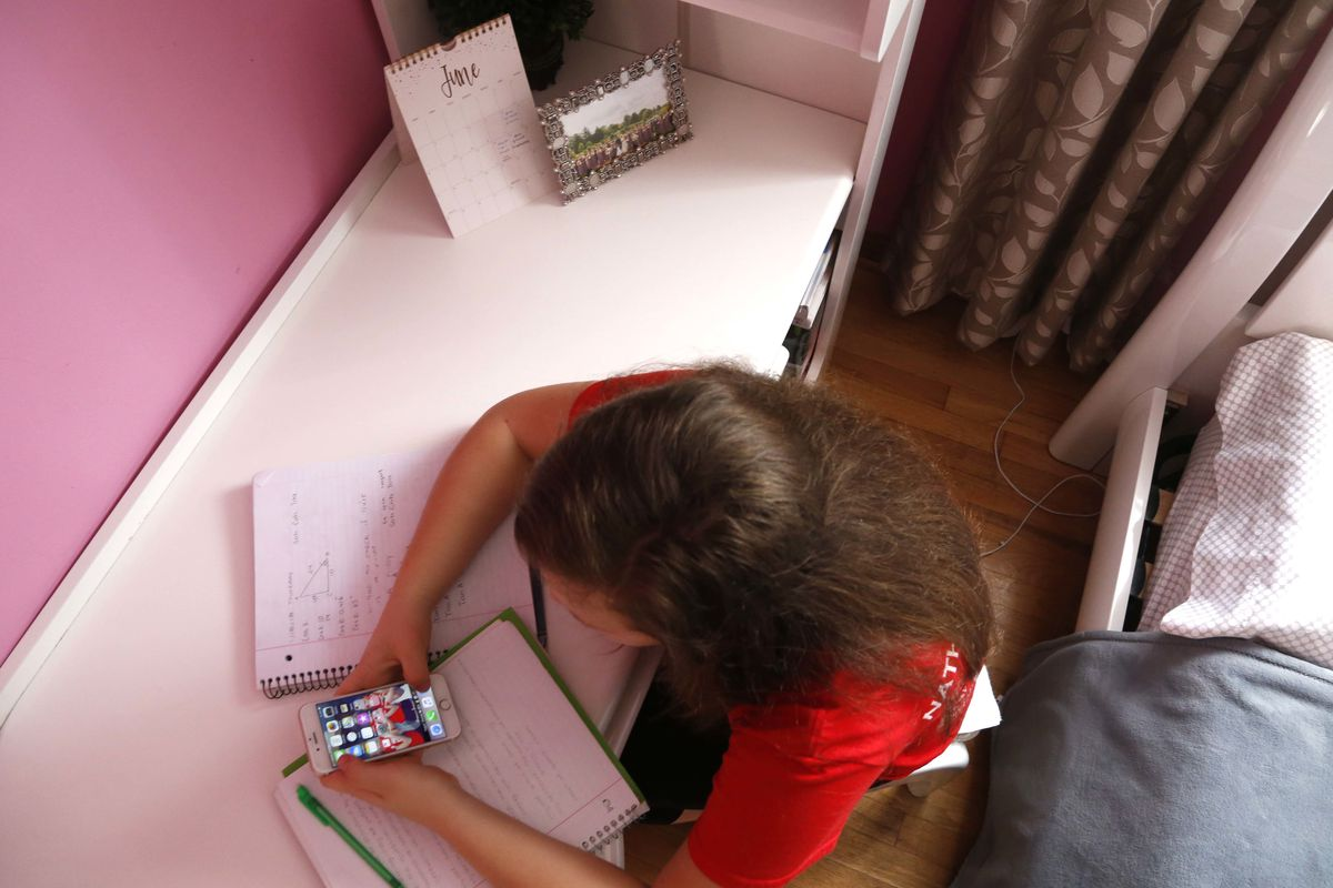Ewelina Cudzich, 13, checks her phone in her Chicago home, Friday, June 8, 2018. Cudzich, who starts high school this fall, says she understands that parents would want to monitor a phone sometimes but thinks teens should be given more freedom as they pro