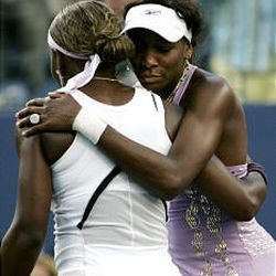 Venus Williams and her sister, Serena, share a hug Sunday following their match at the U.S. Open.