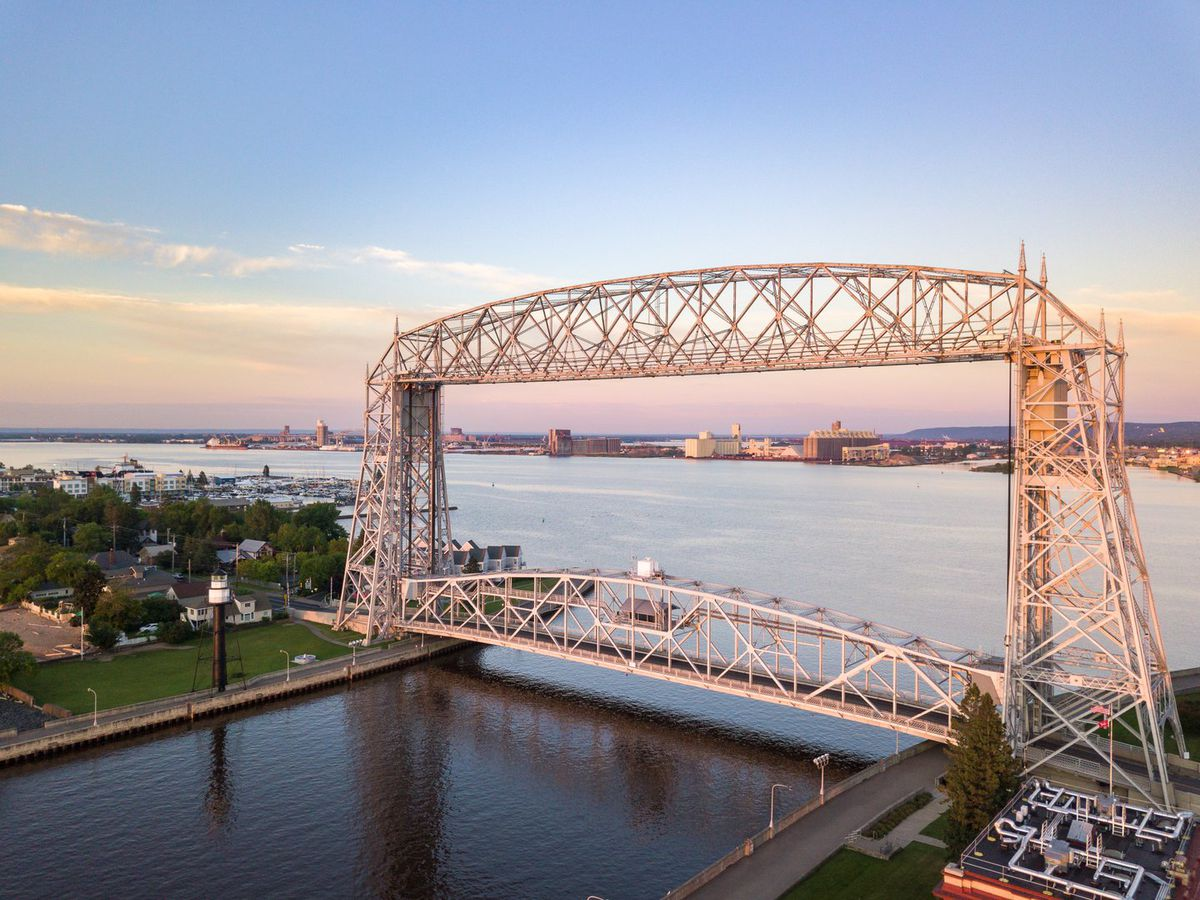 Duluth's iconic aerial lift bridge at Canal Park just as the sun starts to dip below the horizon, turning the sky and waters purple and pink.