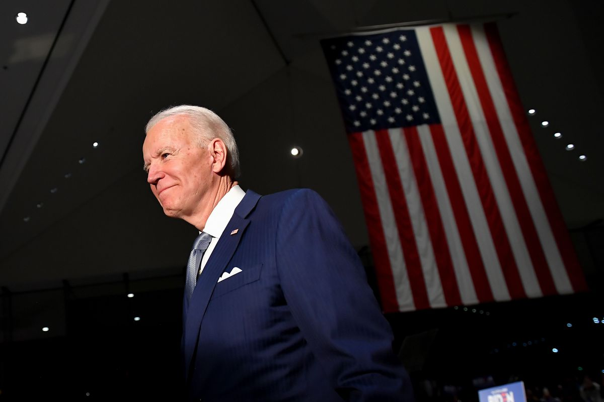 Biden, smiling in a dark blue suit with a crisp white pocket square and silver tie, steps into the spotlight. Behind him, a US flag hangs from the ceiling.