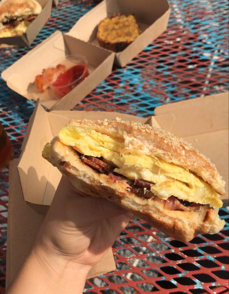 A hold hands a half-eaten sandwich, exposing a cross-section of egg, bacon, cheese, and sauerkraut on a sesame seed bun