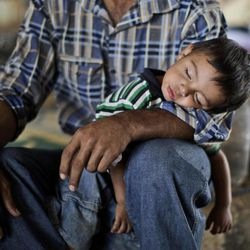 Syrian, Ghassan Khalil, 30, who fled his home in Marea 12 days ago due to Syrian government shelling of his house, holds his sleeping son Mahmoud, 2, who suffers from fever, as they take refuge at the Bab Al-Salameh border crossing in hopes of entering one of the refugee camps in Turkey, near the Syrian town of Azaz, Monday, Sept. 3, 2012.