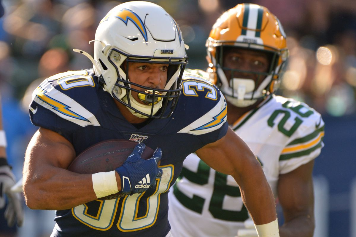 Los Angeles Chargers running back Austin Ekeler is defended by Green Bay Packers defensive back Tony Brown during the second quarter at Dignity Health Sports Park.