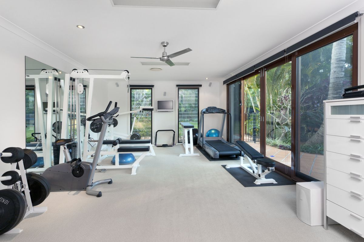 A white walled home gym with many windows at right and far back.