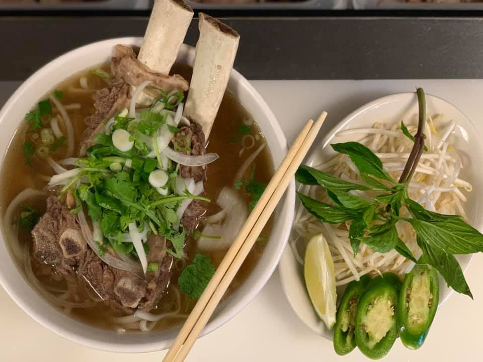 A bowl of pho with shortribs sticking out from the broth, next to a separate bowl of basil, sprouts, lime, and other garnishes