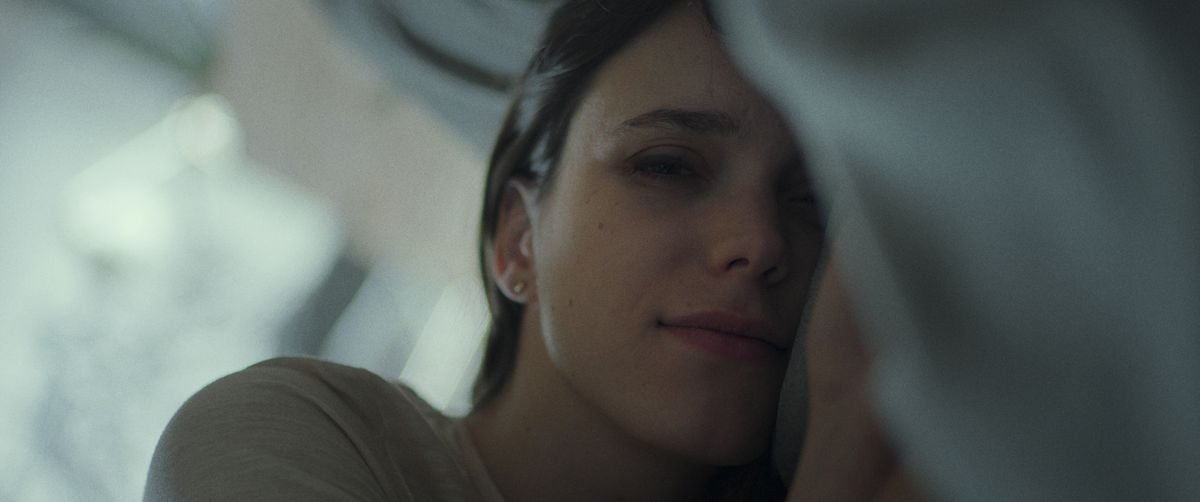 Stacy Martin lies in bed, smiling at the camera in Archive.