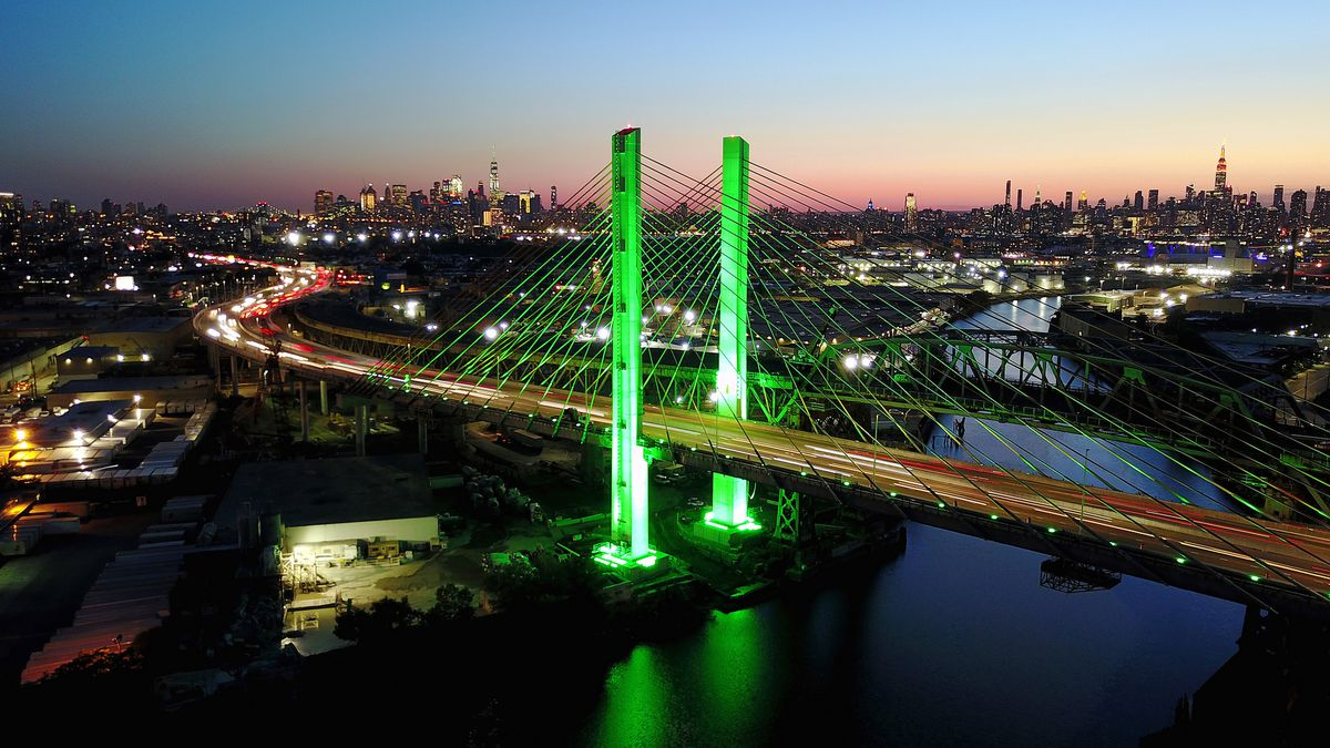 A bridge spanning across a body of water. There is a cityscape in the distance. The bridge is lit in green light. It is sunset and evening.
